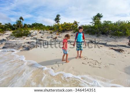 Brother and sister enjoying time at tropical beach of Iguana islands at Exuma Bahamas - stock photo