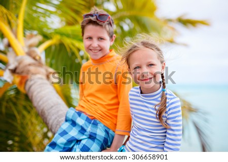 Brother and sister enjoying time at tropical beach sitting on hanging palm - stock photo