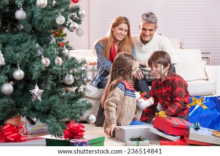 Brother and sister exchanging Christmas gifts in front of their parents. Happy family and holiday concept. - stock photo
