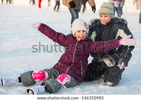 Brother and sister fell while skating and playing with snow - stock photo