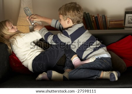 Brother And Sister Fighting Over Remote Control - stock photo