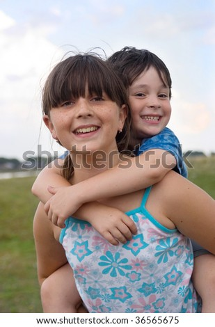Brother and sister (girl ia carrying of biy on the back) - stock photo
