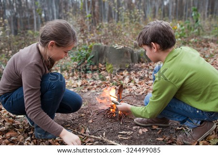 Brother and sister have fun in the woods - stock photo