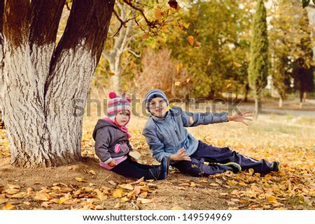 brother and sister having fun in fall park - stock photo
