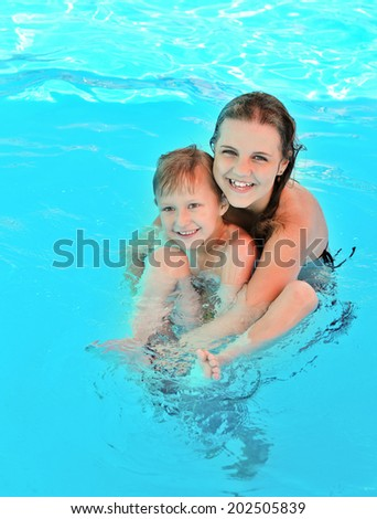 brother and sister having fun in pool - stock photo