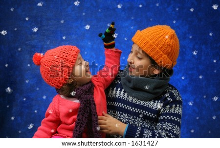 Brother and sister having fun with the snow in winter outfit. Look at my gallery for more winter images