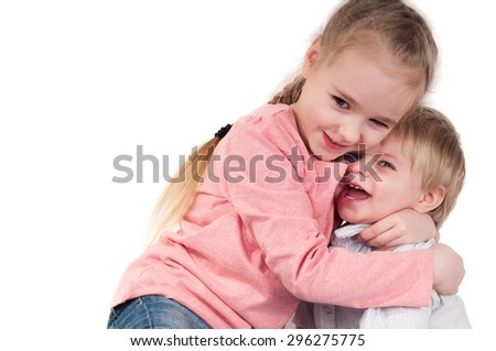Brother and sister hugging in studio, isolated on white - stock photo