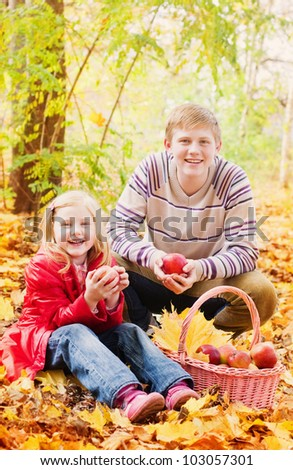 brother and sister in autumn garden - stock photo
