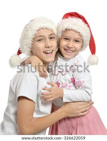 Brother and sister in Christmas hats hugging - stock photo