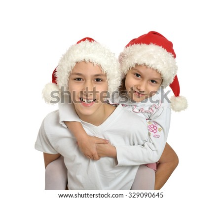 Brother and sister in christmas hats hugging on a white background - stock photo