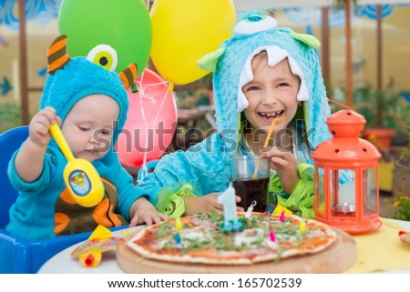 Brother and sister in costumes of monsters having fun in a cafe with pizza and drink - stock photo