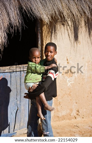 brother and sister in front of a hut  in an african village - stock photo