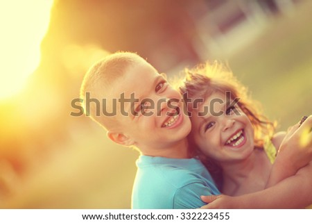 Brother and sister in hug with love and big happy smile. Shallow depth of field. Soft focus.