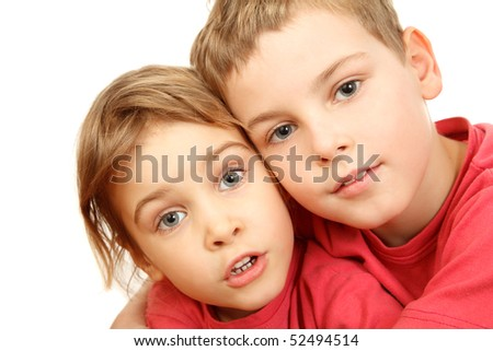 Brother and sister in pink shirts embracing look at camera. Isolated on white background.