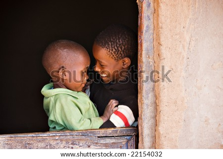 brother and sister in the door of a hut  in an african village - stock photo