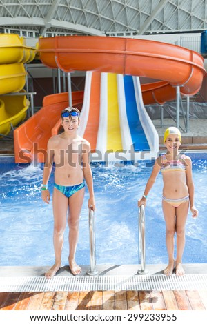 brother and sister in the pool with water slides - stock photo