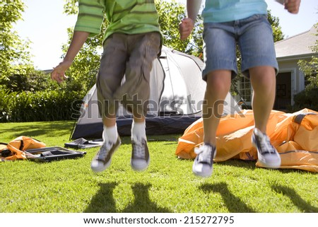 Brother and sister (8-10) jumping in front of incomplete dome tent on garden lawn, low section, front view - stock photo
