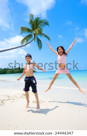 Brother and sister jumping up high while having fun at the sandy beach - stock photo