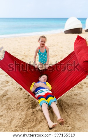 Brother and sister kids relaxing in hammock at tropical beach - stock photo