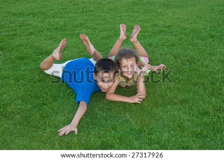 brother and sister lie on the green grass - stock photo