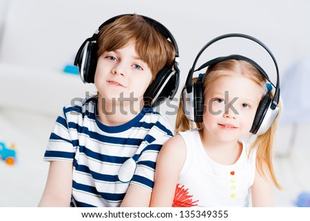 brother and sister listen to music in the living room with headphones - stock photo
