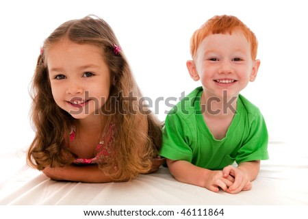 Brother and sister lying on bed with isolated background - stock photo