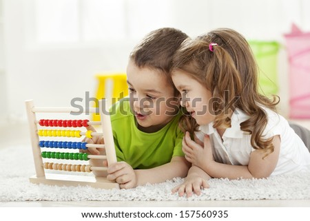 Brother and sister lying  on the floor with abacus, having fun - stock photo
