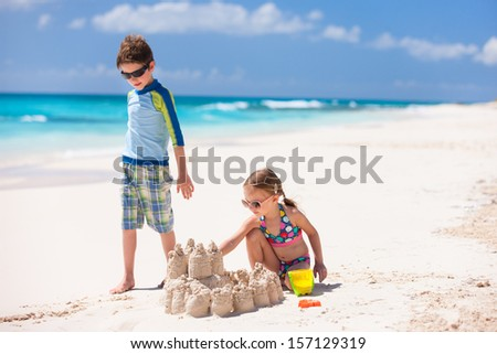 Brother and sister making sand castle at tropical beach