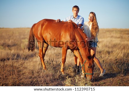 Brother and sister on a field - stock photo