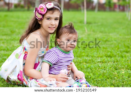 Brother and sister on a green glade - stock photo