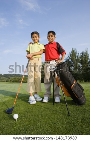 Brother and sister on golf course - stock photo