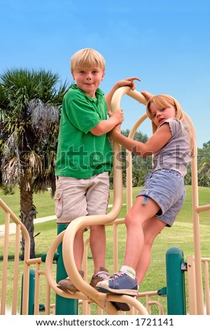 Brother and sister on playground with tropical background - stock photo