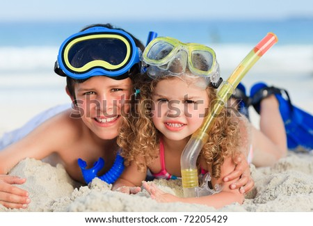 Brother and sister on the beach - stock photo