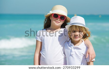 Brother and sister  on the  beach enjoying summer vacation - stock photo