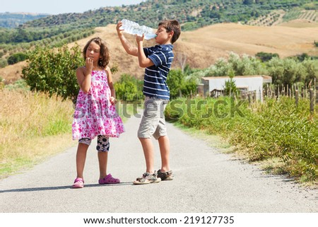 brother and sister on the road drinking water and thinking about the travel