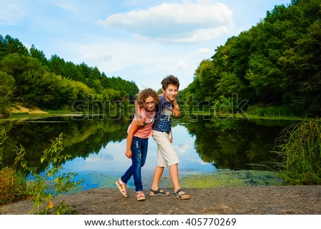 Brother and sister on vacation in green forest with river. Beautiful nature landscape. Family traveling, spending time together. Boy and girl, children, kids, friends having fun outdoors. - stock photo