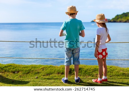 Brother and sister outdoors at tropical coast on summer vacation - stock photo