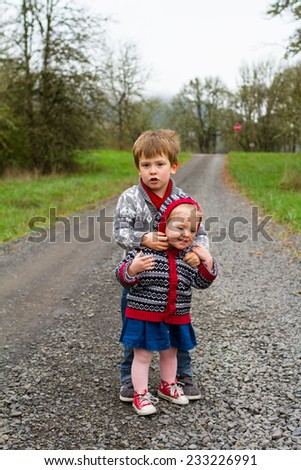 Brother and sister outdoors in a fashion family lifestyle portrait of the two children. - stock photo