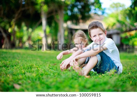 Brother and sister outdoors on summer day - stock photo