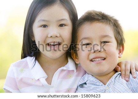 Brother and sister outdoors smiling - stock photo