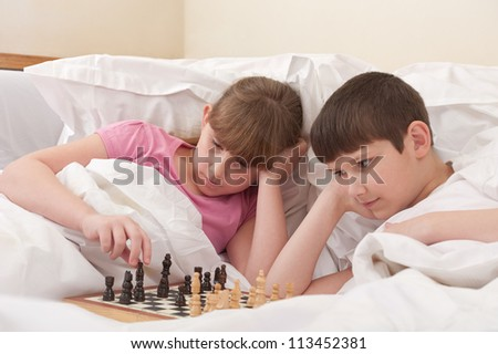 brother and sister play chess in bed, indoors
