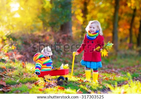 Brother and sister play in autumn park with golden leaves. Baby boy in a wheel barrow. Two kids, boy and girl walk in the forest on a sunny fall day. Children playing outdoors with yellow maple leaf