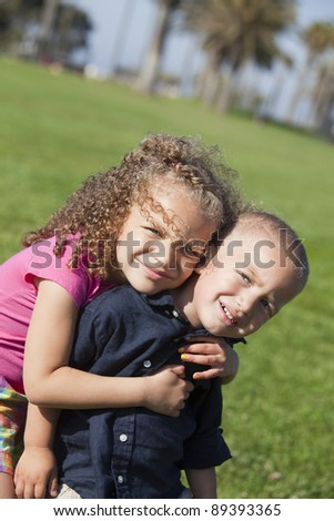 Brother and sister playing at a park - stock photo