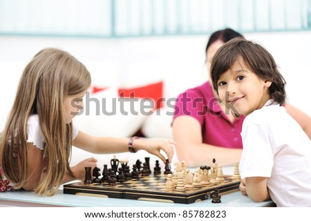 Brother and sister playing chess at home with their mother - stock photo