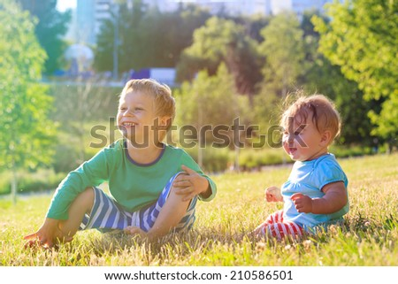 brother and sister playing in summer park