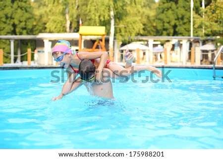 Brother and sister playing in the pool, the boy raised his sister on his shoulders - stock photo
