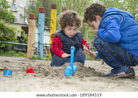 Brother and sister playing in the sand with a bucket and spade on the playground. - stock photo