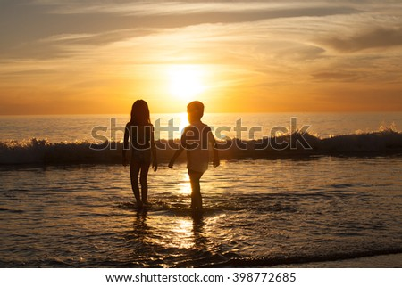 Brother and sister playing on the beach - stock photo