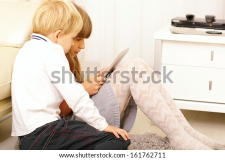 Brother and sister playing on their tablet computer