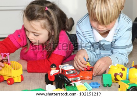 Brother and sister playing quietly - stock photo
